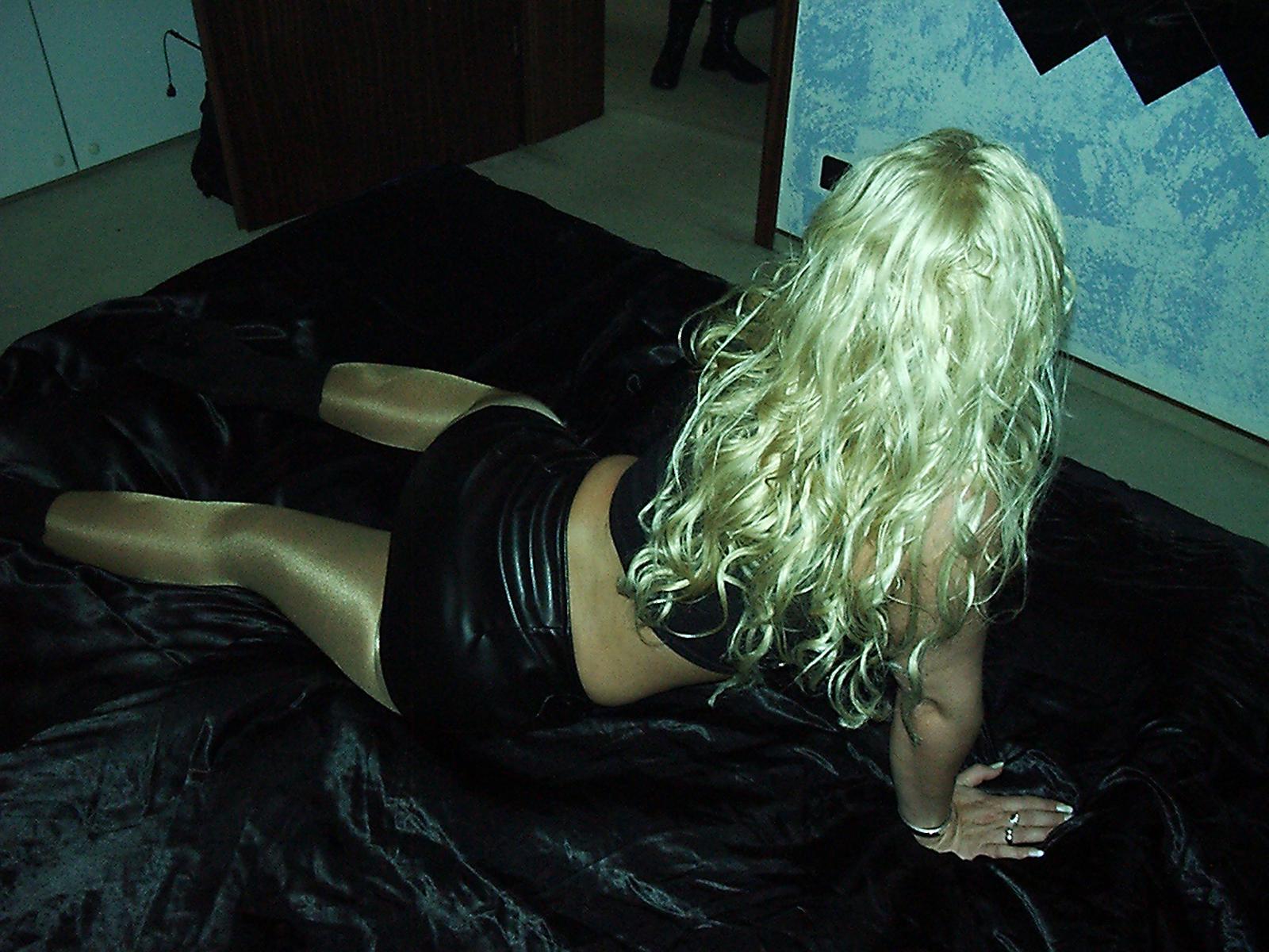 Strohblonde Blondine mit dem Rücken zur Kamera liegt auf dem Bett